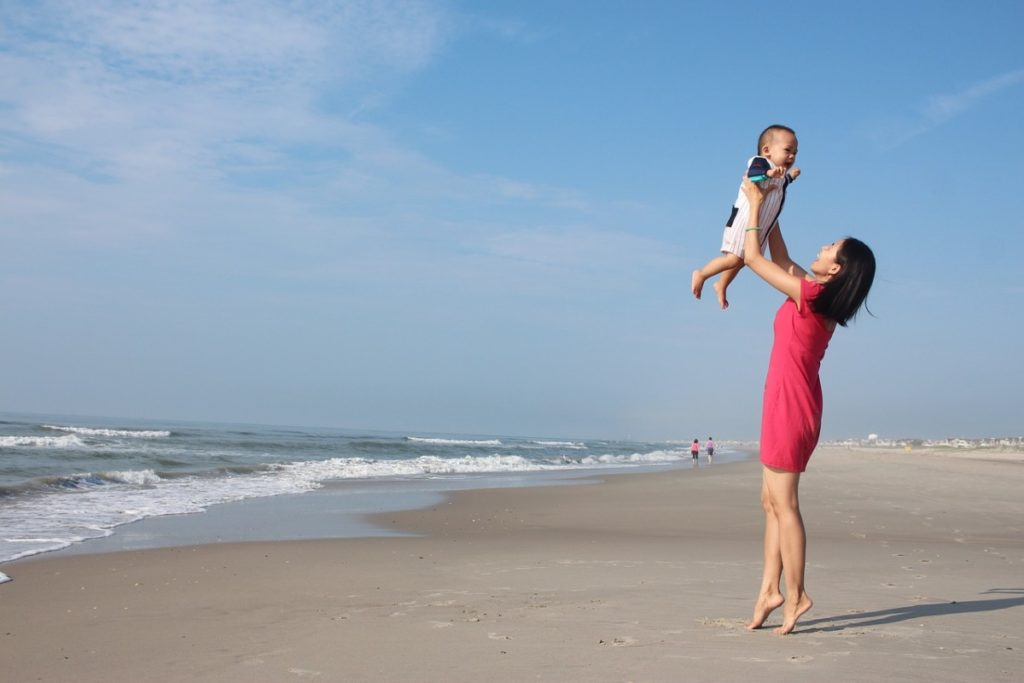 mother tossing baby in air