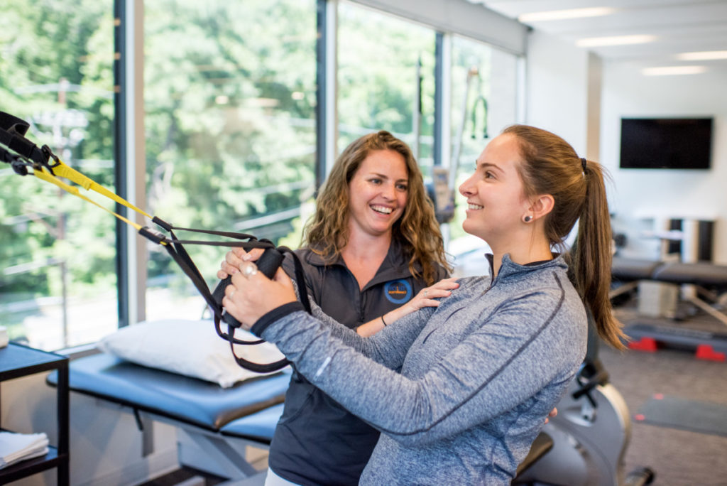 Physical therapist in Bethesda, MD working with patient on arm strengthening machine